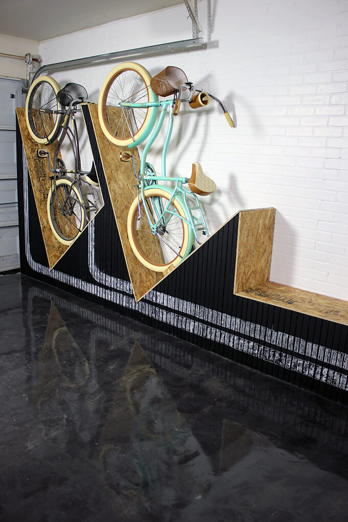 A unique way to store your bikes in the garage - a DIY wall-mounted bike rack with a bench. It takes up little space depth wise, you can store two bikes, it gives you a place to sit down AND the front is painted with chalkboard paint so the front design can always change.
